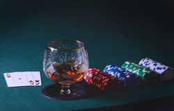 Poker table with glass of cognac, casino chips and playing cards. Vintage tonned photo Stock Images