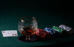 Poker table with glass of cognac, casino chips and playing cards Stock Images