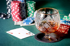 Poker table with glass of cognac, casino chips and playing cards Stock Photos
