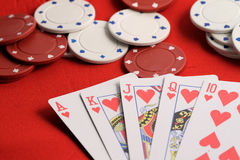 Poker table royal flush. Royal flush from a poker game on a red table with Ace king queen jack ten of hearts stock photography