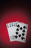 Poker table with royal flush. A red poker table with royal flush. The light in the scene is spot like Stock Photography