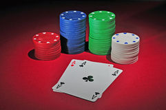 Poker table with two aces. Several stacks of casino chips of various heights and colors with two aces, a black and a red one, all sitting on a red colored Stock Image