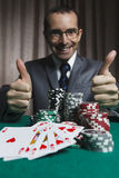 Poker winner, businessman won poker game. Royal flush on casino table  man won,  show thumbs up Royalty Free Stock Photos