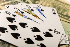 Poker winning hand over dollar bills. Royal flush in spades over twenty dollar bills Royalty Free Stock Images