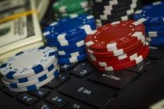 Pokerchiper och packar av dollar på en bärbar dator royaltyfria bilder