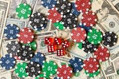 Pokerchiper och tärning på en hög av dollar segra för begrepp fotografering för bildbyråer