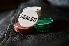 Pokerchips mit Händler-Chip auf strukturiertem Hintergrund stockfotografie
