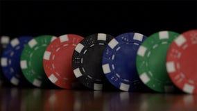 Pokerchips stehen in Folge auf einem schwarzen Hintergrund, ein Domino-Effekt Spielend sind Pokerchips auf dem Tisch, ein Symbol  lizenzfreie stockbilder
