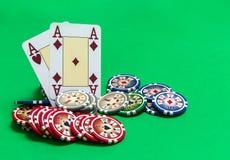 Pokerchipstapel und Spielkarten auf grüner Tabelle lizenzfreie stockfotografie