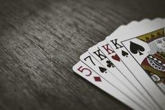 Pokerhänder - tre av en sort Closeupsikt av fem spela kort som bildar poker tre av en sorthand Royaltyfri Bild