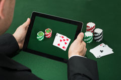 Pokerhand med den Digital minnestavlan som visar Chips And Cards royaltyfri fotografi