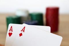Pokerhand mit zwei Assen vor Stapel stockbilder