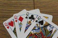 Pokerkarten auf einem hölzernen backround, Satz Königinnen von Vereinen, Diamanten, Spaten und Herzen Lizenzfreies Stockbild