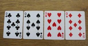 Pokerkarten auf einem hölzernen backround, Satz nines von Vereinen, Diamanten, Spaten und Herzen stockfotos
