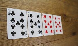 Pokerkarten auf einem hölzernen backround, Satz nines von Vereinen, Diamanten, Spaten und Herzen lizenzfreie stockbilder