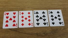 Pokerkarten auf einem hölzernen backround, Satz nines von Vereinen, Diamanten, Spaten und Herzen lizenzfreie stockfotos