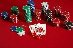 Pokerkarten und spielende Chips auf rotem Hintergrund Stockfoto