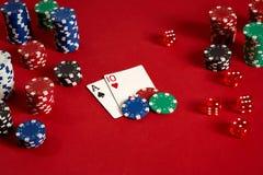 Pokerkarten und spielende Chips auf rotem Hintergrund Stockfotos