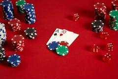 Pokerkarten und spielende Chips auf rotem Hintergrund Stockbilder