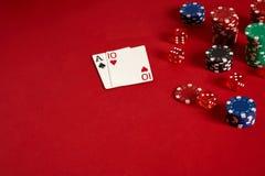 Pokerkarten und spielende Chips auf rotem Hintergrund Stockbild