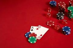 Pokerkarten und spielende Chips auf rotem Hintergrund Stockfotografie