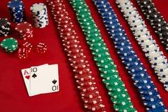 Pokerkarten und spielende Chips auf rotem Hintergrund Lizenzfreies Stockfoto