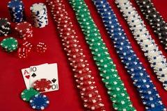 Pokerkarten und spielende Chips auf rotem Hintergrund Lizenzfreie Stockfotos