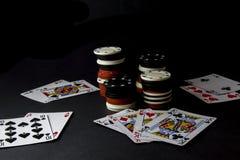 Pokerkort och buntar, lott av chiper över svart Alla in, fyra av arkivfoton