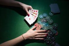 Pokerkort och chiper i hand på grön bakgrund Arkivfoto