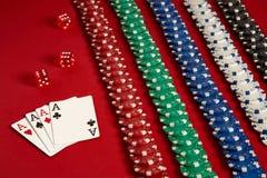 Pokerkort och dobblerichiper på röd bakgrund Royaltyfri Foto