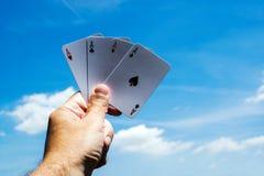 Pokerkort på bakgrunder för blå himmel hand för överdängare fyra arkivfoton