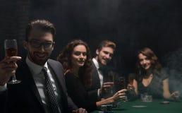Pokerspelare med ett exponeringsglas av vin som sitter på en tabell royaltyfria foton