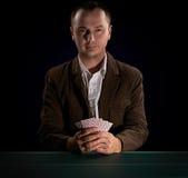Pokerspelare på en mörk bakgrund Arkivfoto