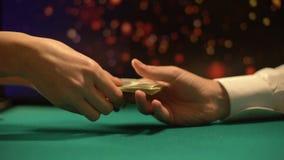 Pokerspelare som ger pengar till den kvinnliga croupier som köper spela chiper, kasino arkivfilmer