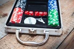 Pokeruppsättning i metalliskt fall på trägolv Arkivfoto
