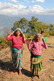 POKHARA, ΝΕΠΑΛ - 5 ΙΑΝΟΥΑΡΊΟΥ 2015: Δύο νεπαλικές γυναίκες που φέρνουν ένα καλάθι στην πλάτη τους κοντά σε Pokhara με τα βουνά το Στοκ Φωτογραφία