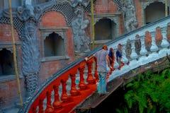 POKHARA, ΝΕΠΑΛ ΣΤΙΣ 10 ΟΚΤΩΒΡΊΟΥ 2017: Μη αναγνωρισμένοι άνθρωποι που χρωματίζουν τα σκαλοπάτια με το κόκκινο μέσα Gupteshwor, Νε Στοκ Εικόνες