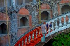 POKHARA, ΝΕΠΑΛ ΣΤΙΣ 10 ΟΚΤΩΒΡΊΟΥ 2017: Μη αναγνωρισμένοι άνθρωποι που χρωματίζουν τα σκαλοπάτια με το κόκκινο μέσα Gupteshwor, Νε Στοκ Φωτογραφία