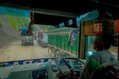 POKHARA, НЕПАЛ 10-ОЕ ОКТЯБРЯ 2017: Закройте вверх водителя автобуса от cabain управляя тележкой на дороге в улицах Стоковые Изображения RF
