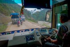 POKHARA, НЕПАЛ 10-ОЕ ОКТЯБРЯ 2017: Закройте вверх водителя автобуса от cabain управляя тележкой на дороге в улицах Стоковая Фотография