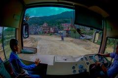 POKHARA, НЕПАЛ 10-ОЕ ОКТЯБРЯ 2017: Закройте вверх водителя автобуса от cabain управляя тележкой на дороге в улицах Стоковое Фото