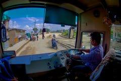 POKHARA, НЕПАЛ 10-ОЕ ОКТЯБРЯ 2017: Закройте вверх водителя автобуса от cabain управляя тележкой на дороге в улицах Стоковая Фотография RF