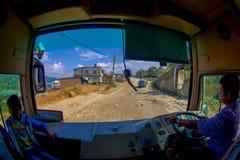 POKHARA, НЕПАЛ 10-ОЕ ОКТЯБРЯ 2017: Закройте вверх водителя автобуса от cabain управляя тележкой на дороге в улицах Стоковое Изображение