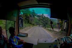 POKHARA, НЕПАЛ 10-ОЕ ОКТЯБРЯ 2017: Закройте вверх маленького ребенка с водителем автобуса в cabain управляя тележкой на дороге Стоковая Фотография RF