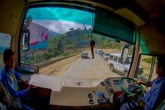POKHARA, НЕПАЛ 10-ОЕ ОКТЯБРЯ 2017: Закройте вверх маленького ребенка с водителем автобуса в cabain управляя тележкой на дороге Стоковое Изображение RF