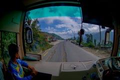 POKHARA, НЕПАЛ 10-ОЕ ОКТЯБРЯ 2017: Закройте вверх маленького ребенка с водителем автобуса в cabain управляя тележкой на дороге Стоковые Изображения