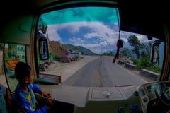 POKHARA, НЕПАЛ 10-ОЕ ОКТЯБРЯ 2017: Закройте вверх маленького ребенка с водителем автобуса в cabain управляя тележкой на дороге Стоковая Фотография