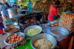 POKHARA, НЕПАЛ 10-ОЕ ОКТЯБРЯ 2017: Закройте вверх asorted еды, лапшей, салата и яичек внутри металлических подносов в a Стоковая Фотография