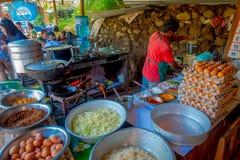 POKHARA, НЕПАЛ 10-ОЕ ОКТЯБРЯ 2017: Закройте вверх asorted еды, лапшей, салата и яичек внутри металлических подносов в a Стоковое Фото