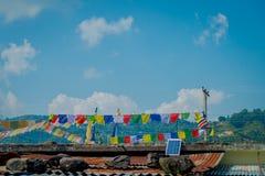 POKHARA, НЕПАЛ - 6-ОЕ ОКТЯБРЯ 2017: Красивый внешний взгляд красочных флагов над корни здания, в Pokhara, Непал Стоковые Изображения RF